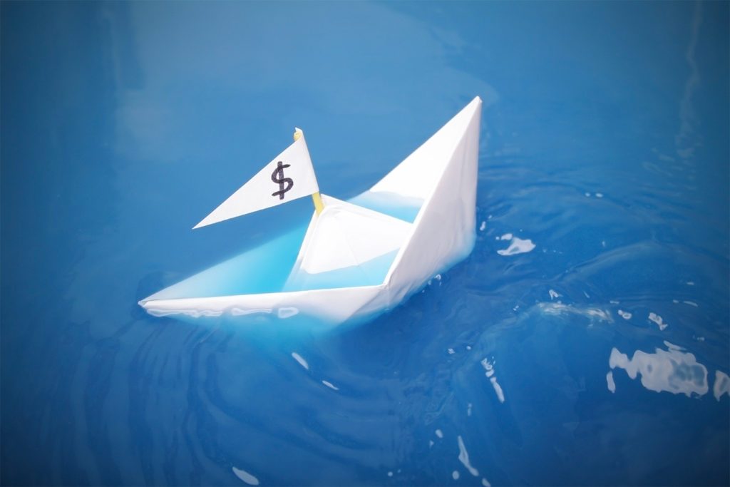 paper boat with a dollar sign on its flag is sinking in blue water